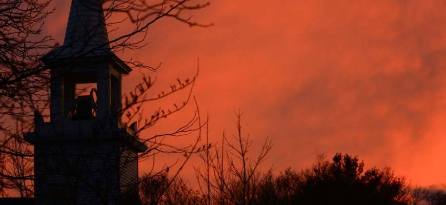 Kerktoren met oranje lucht bij zonsopkomst