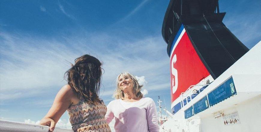Moeder en dochter reizen op buitendek ferry met blauwe lucht